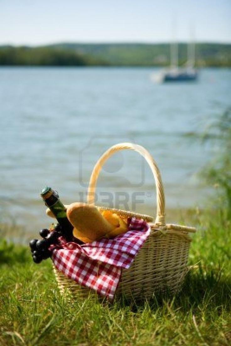 Panier pique-nique avec de la nourriture et une bouteille de cidre à proximité de leau Banque dimages