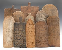 "AFRICAN ARTEFACTS: Used by students in West Africa to practice Arabic calligraphy and learn the teachings of the Qur'an, these eleven teaching tablets have Arabic writing and diagrams on both sides. The tablets are smooth from use as the students wash off the charcoal ink they use to write and re-use them many times. They are semi-antique in age and range from 14"" to 26"" in length (Aspire Auctions)."