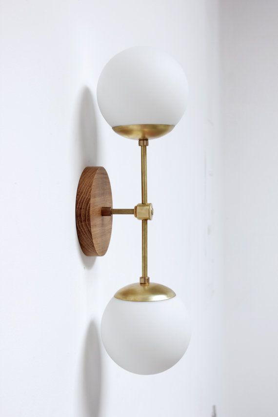 The Northern Sconce (double) is a nod to midcentury modern lighting with the large matte white glass globes and brass arms. This wall sconce is a true statement piece.   -6 diameter x 1 tall oak or walnut hardwood base  -Base is cut and sanded to a silky finish and sealed with beeswax  -Two keyholes in back for hanging  -Raw brass arms and joint  -Two 7 mid century modern style matte white glass globe shades  -Fixture 25 long, 8 from wall at globes  -Fixture can be hardwired or built with…