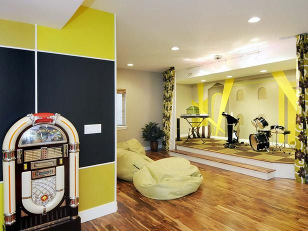 This colorful, eclectic media room features an entertainment area complete with a stage. From HGTVRemodels.com.  We have kids who are very talented and want a small stage in our media room with a screen that comes down for amazing movie viewing.  Kind of fun...