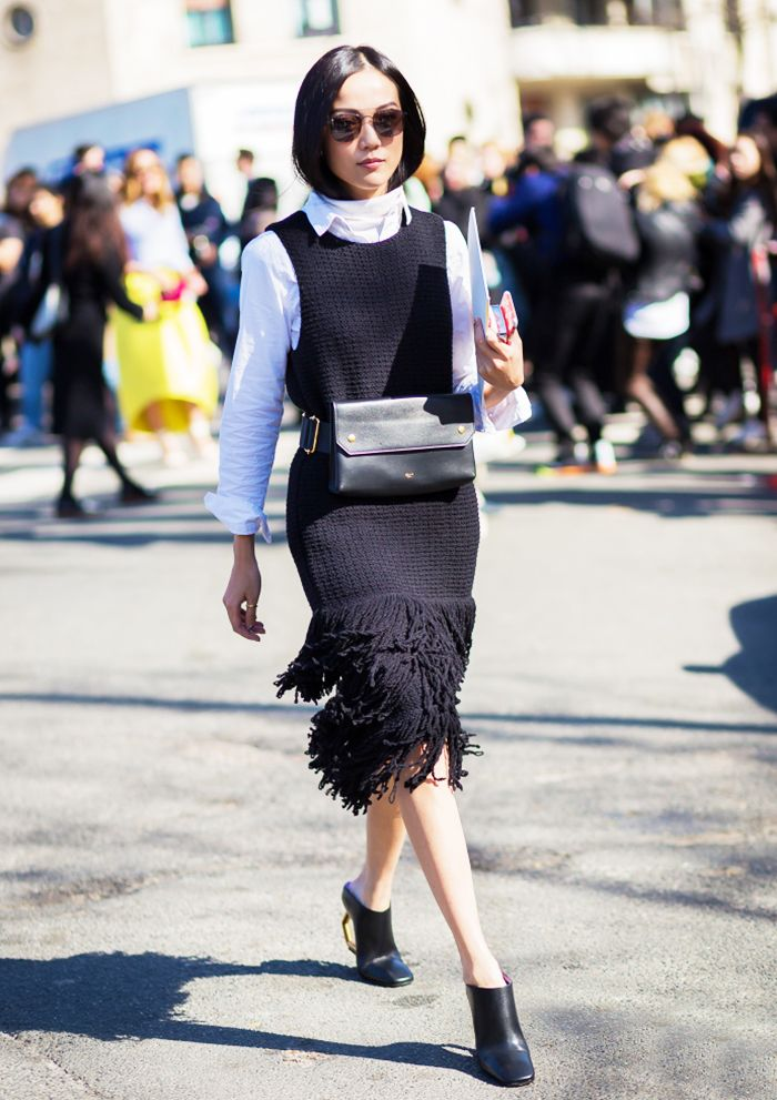 Yoyo Cao in a black Celine Fringed Dress and black leather mules; paired with a calfskin Bumbag