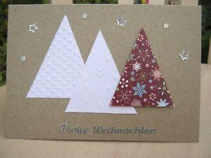 """Handgefertigte Weihnachtskarte mit passendem weißen Umschlag.  - Kraftpapier-Optik (225 g/qm; 75% Altpapier und 25% Holzschliff) - drei aufgeklebte Tannenbäume (Dreiecke) aus Karton - davon zwei weiße geprägt und ein Baum mit weihnachtlichem Motiv - silberner Reliefaufkleber """"Frohe Weihnachten"""" - silberne Sternchen"""