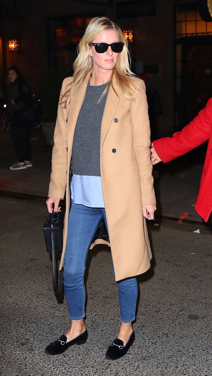 Always put together, Nicky Hilton Rothschild stepped out in this preppy combo featuring a chic camel coat. She paired the wool topper with a layered sweater, structured leather handbag, oversized wa...