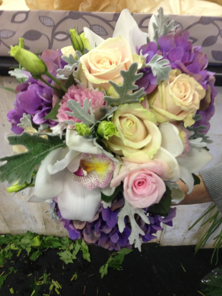 A mixed bouquet of roses, cymbidium orchids, hydrangea, lisianthus, and greenery.