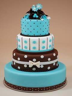 Four tier chocolate brown and blue polka dot fondant wedding cake. Decorated with brown, white and small and large polka dots and rolled fondant bows. The wedding cake topper is made with blue and chocolate brown buttercream, then garnished with blue silk flowers.