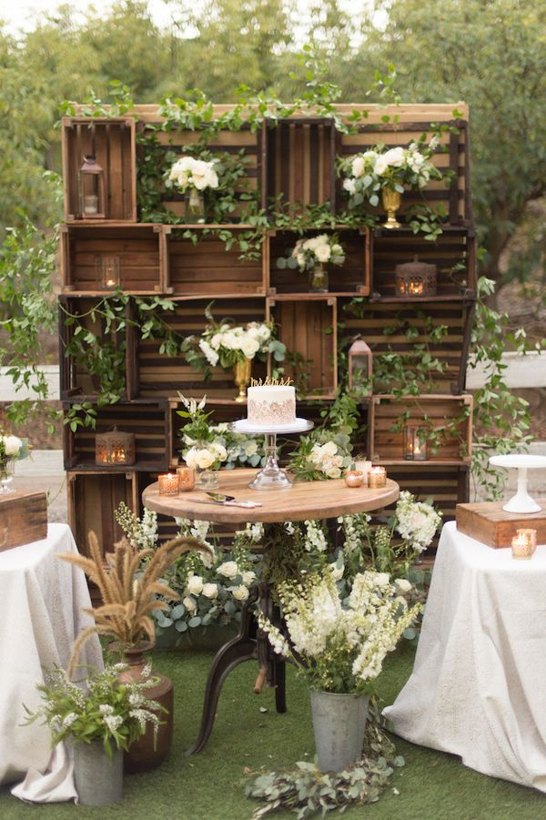 """Can a beautiful backdrop be as easy as just placing vases of flowers at different heights? Sure! This rustic crate setup allows you to just place a number of arrangements in the """"cubbies"""", no taping, cutting, or gluing required."""