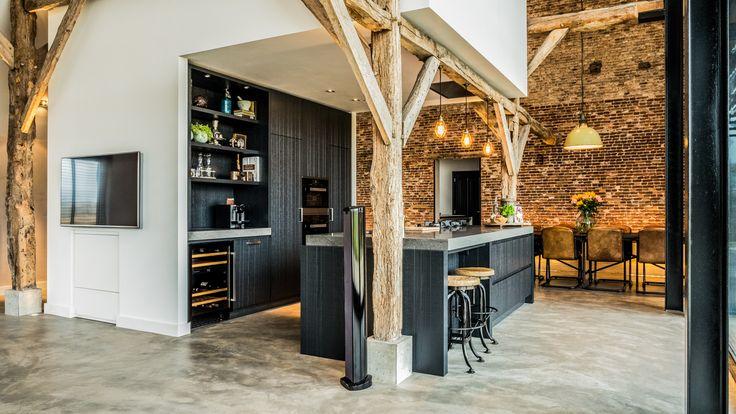 Het kookeiland met kastenwand ingepast tussen de houten spanten. een heerlijke plek om lekker te koken en borrelen.
