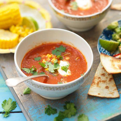 1 Fruit in een grote soeppan de lente-uimet de steeltjes van de koriander en deknoflook. Voeg de in stukken gesnedenpaprika, de tomaat en de pepertjes toe enbak even mee. Giet er 500 ml water bij enbreng aan de kook. Laat 10...