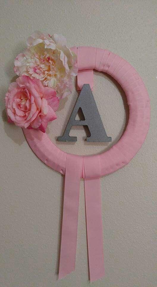 Adorno para la pared de un cuarto de niña hecho con letra de madera, flores, corona de metal y cinta