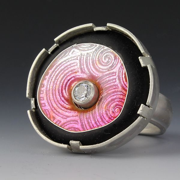 Floating Circle Ring in Light Pink by Jennifer Park. This ring is made of cloisonne enamel set in silver with a 4mm cubic zirconia in the center. The 6mm sterling shank is rounded on the inside for comfort. Matte black enamel contrasts dramatically with soft pink glossy enamel.