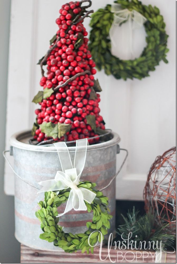 Pretty rustic Christmas vignette with boxwood wreaths and a cranberry topiary in a minnow bucket. by Unskinny Boppy