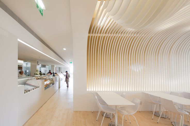 At Gondodoce, a minimalist bakery in Gondomar, Portugal, Paulo Merlini Arquitectura created undulating wood ceilings reminiscent of swoops of cake frosting. They don't just look beautiful—the design also helps reduce heat and refract light. Avenida Dr. Mário Soares, Gondomar, Portugal