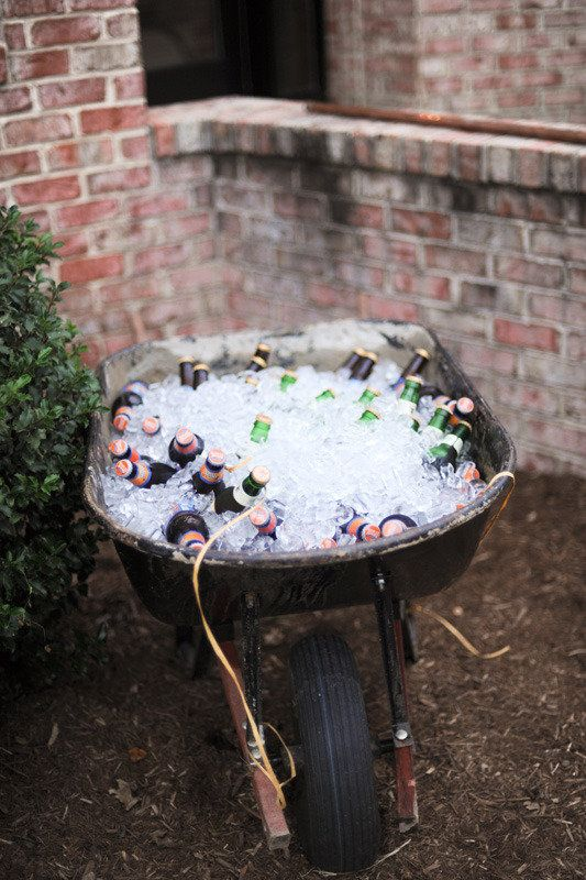 A wheel barrow full of drinks for an outdoor party.