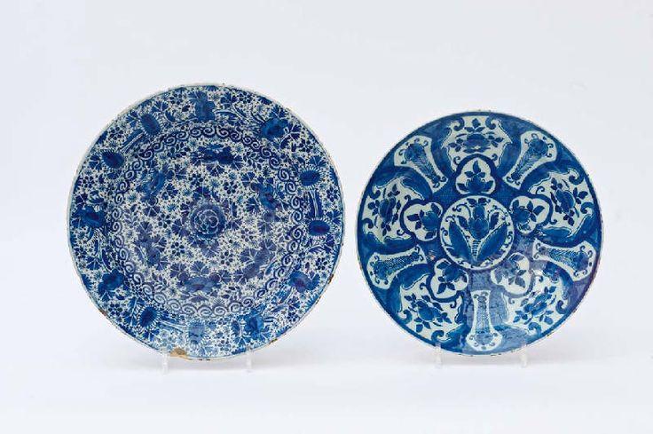 Twee Delfts blauw aardewerk ronde schotels    18e eeuw, ��n gemerkt De Paeuw  met een floraal decor in panelen, de ander met een vol lotusdecor (schilfers, laatste met barst). (2) D 30 en 34 cm