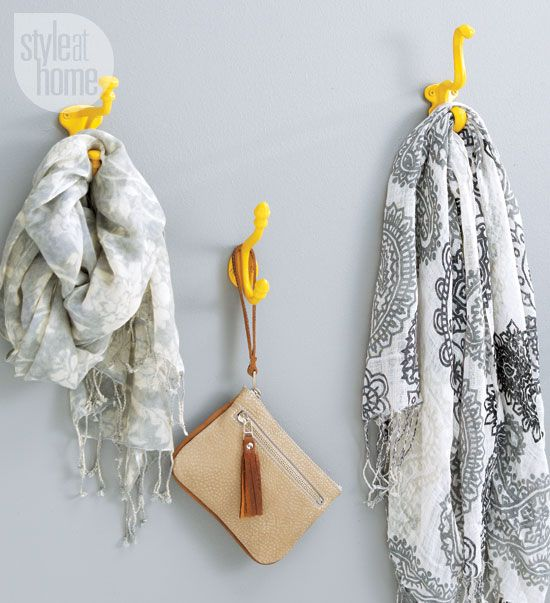 Bright yellow spray paint unifies a collection of eclectic wall hooks for a dramatic statement in the front hall.