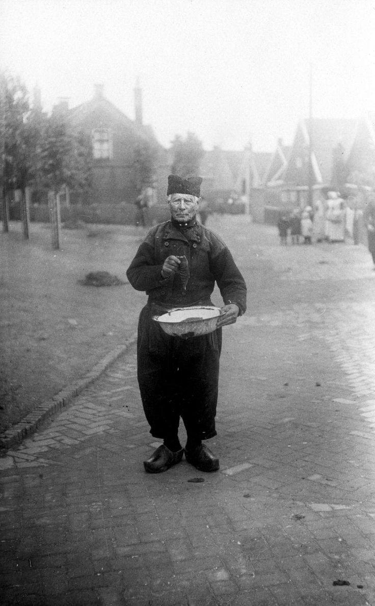 Klederdrachten : Tijdens een bezoek van Koningin Wilhelmina aan Urk staat een man in klederdracht op straat met een metalen bak en een vis in de hand. 1921 #Urk