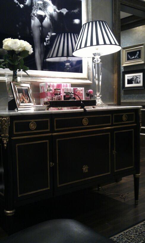 black & gold dresser, black & white Lucite lamp, fresh white roses, black & white pics.