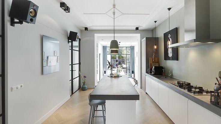 Deze op maat gemaakte keuken is ontworpen door BNLA architecten in Amsterdam. De  industriële en robuust ogende keukenbladen bestaan uit mdf afgewerkt met beton ciré. De grote stalen pui en de verbinding van de keuken met de eetkamer in de aanbouw brengen veel licht en lucht in de woning.  Fotografie: Wim Hanenberg.