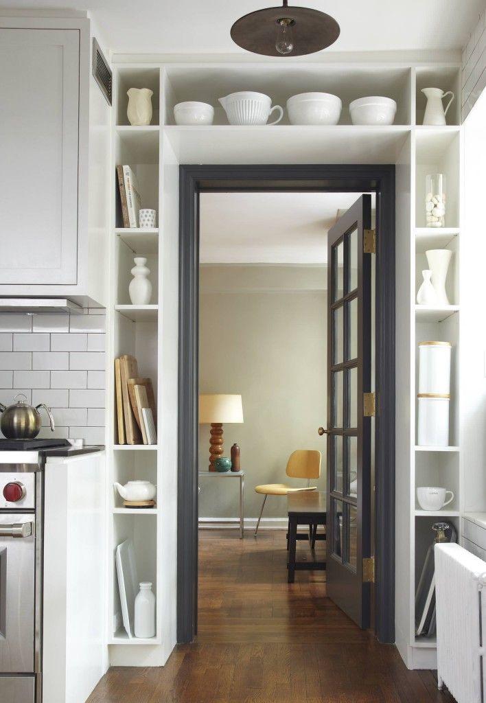 Вокруг входной двери обычно много свободного пространства. Чаще всего ограничиваются устройством антресолей над дверью, но можно обрамить дверной проем полками во всю высоту