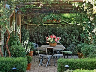 Gorgeous pergola. Love all the layers of shrubs, potted plants, hedges, vines. Also love the gravel teamed with aged timber furniture