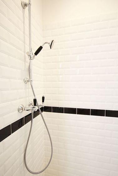 Un carrelage métro avec une frise noire dans la douche