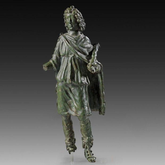 """Romeinse keizertijd, 2e eeuw na Chr. Dendrophoros (een epitheton van Sylvanus = Lat. """"van het bos""""). Tutelar van bossen en velden. Een college van priesters die droeg takken van bomen in processie ter ere van een goddelijkheid. Hoogte 15,8 cm. Bronzen figur van een langharige jongeman dragen van broeken, een knie-lange tuniek en een mantel van dezelfde lengte. In de hoek rechts is een snelgroeiende boom boomstammen. Perfecte staat met ongerepte groene patina, rechterhand en rechtervoet…"""