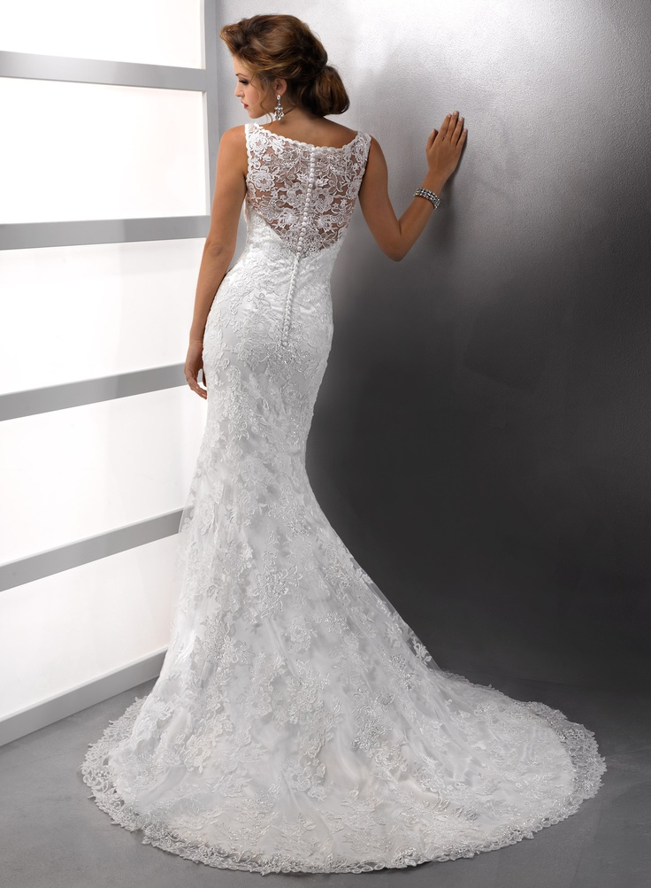 Justina - Elegantly sophisticated, the delicate scoop illusion neckline of this romantic sheath renders this gown unforgettable. Hand beaded lace motifs dance across tulle over Demir Stretch Satin all the way to the hemline, while covered buttons add the perfect finish to the zipper back closure. $1249.00