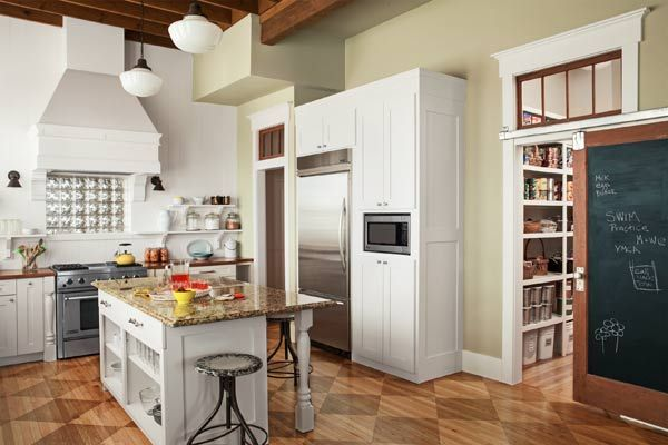 Douglas fir beams, a sliding barn door and a stained checkerboard floor are among the personal touches that distinguish the kitchen of our 2013 Whole-House Remodel winners. | Photo: Lisa Romerein | thisoldhouse.com