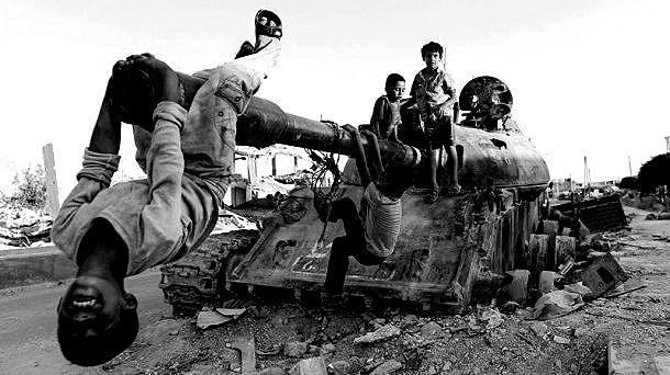 Kobani. Niños jugandos obre los restos de un carro de combate. Foto: EFE