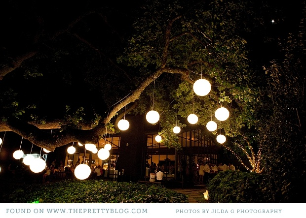 Lanterns hanging from tree branches - creates a romantic ambiance