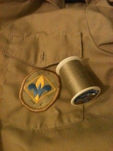 How to sew on a Scout badge in 7 years or less.  Hmmm. I will have to teach this method to the scouts.