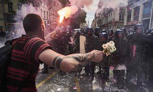 A man holds a bouquet of flowers and a torch as he faces riot police during a demonstration in Lyon, central eastern France. May 2016