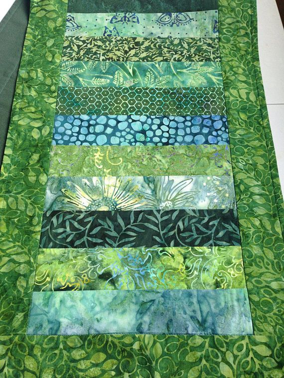 A beautiful table runner made with 11 different batik fabrics in shades of green. Dimensions are 47 x 14. The table runner reverses to a solid dark green cotton backing. Machine wash and dry cool. Fabrics are prewashed and preshrunk.