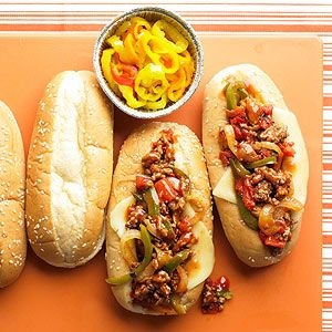 Mozzarella-Provolone Sausage Grinders - peppery Italian sausage and garlic-seasoned onions, topped  with gooey mozzarella or provolone cheese and banana peppers.