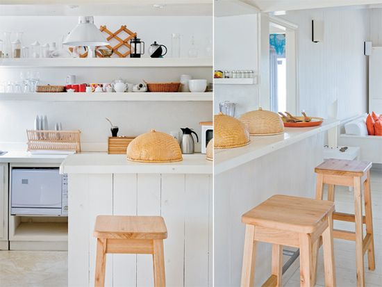 Cocina con barra de madera pintada de blanco y acompañada por dos banquetas (Mario Vico). Estantes de madera. Bajo-mesada, de pino pulido y pintado