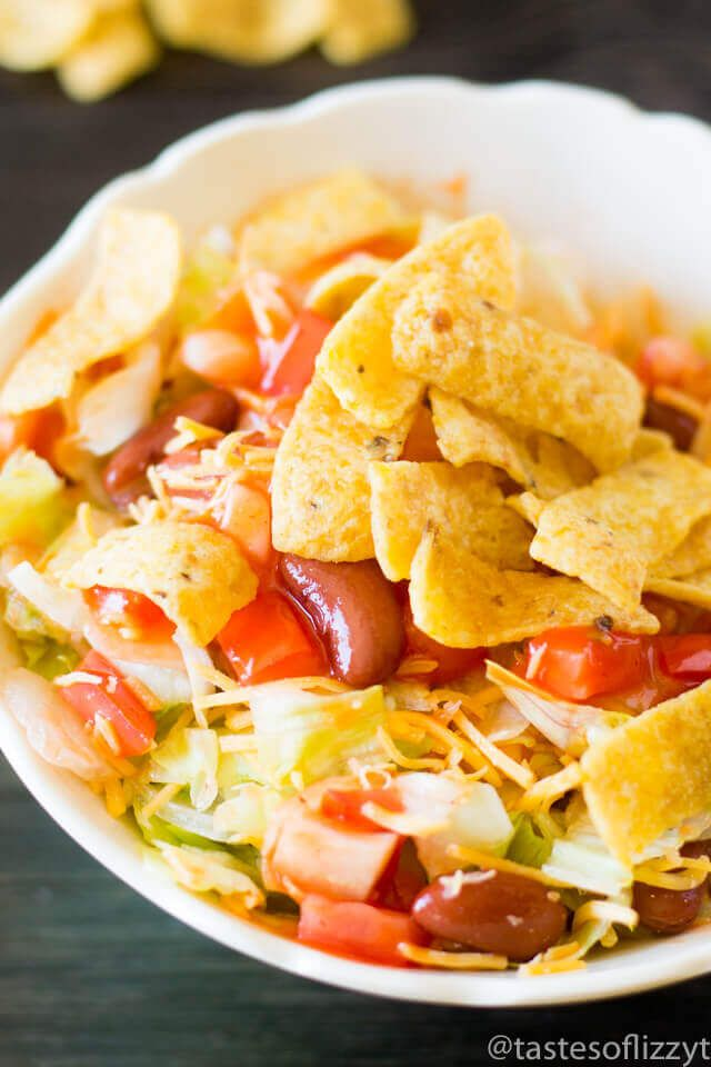 This vegetarian Frito Taco Salad comes together quickly by using bottled dressing. It's full of tomatoes, onions, cheese, lettuce and beans and has crunchy Fritos mixed in!