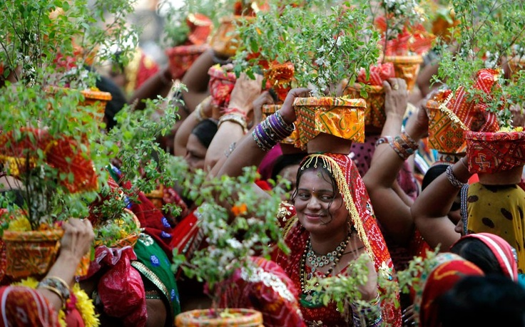 Women carry holy basil plants (Ocimum tenuiflorum) on their heads during a religious procession  in Hyderabad