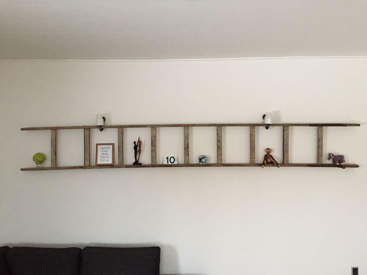 Gammel træstige som reol på væg. Ophængt på gamle strøm-porcelænsklokker.