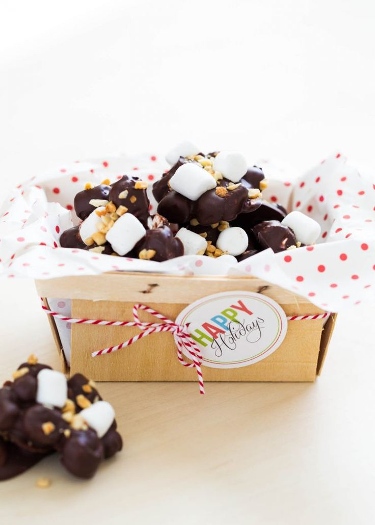 Rocky Road Candy packaged in a wooden basket with parchment paper, bakers twine and a free printable Happy Holidays gift tag. Super easy to make and only takes 5 ingredients! The best part about this recipe is there is absolutely no cooking or baking required.  Perfect for when you need a last minute holiday treat.