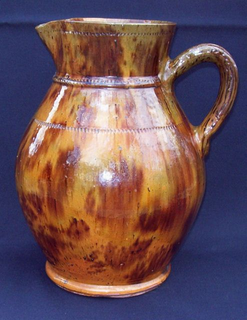 "Redware water or milk pitcher made by Jacob Medinger of Limerick Township, Montgomery County, PA circa 1920. The Medinger Pottery was founded by Jacob's father William in 1872 and remained operational until Jacob's kiln related death in 1932. Exceptional form and glaze with the signature Medinger ribbed handle and coggled rim, neck and shoulder. A really good and somewhat rare example of Medinger pottery. Height - 11 1/2""."