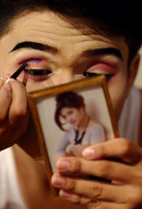 Aktor Aekchai Rachan robi kolorowy makijaż przed występem w buddyjskiej świątyni w Bangkoku. Likay jest popularną formą muzycznego teatru ludowego w Tajlandii. Aktorzy, mężczyźni i kobiety noszą ekstrawaganckie stroje bogato ozdobione cekinami i brokatem.  http://www.tvn24.pl/zdjecia/zdjecie-dnia,46897,lista.html