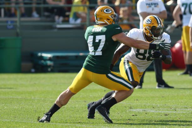 Green Bay Packers linebacker Jake Ryan holds up Green Bay Packers running back Ty Montgomery during Packers training camp at Ray Nitschke Field on...