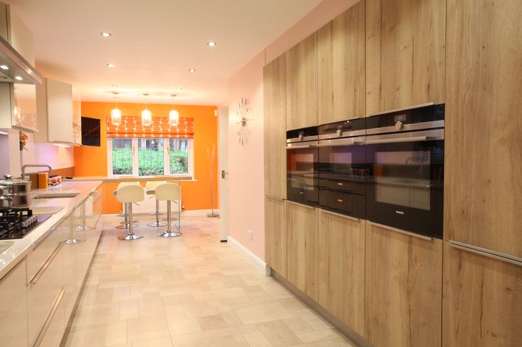Gloss Ivory kitchen with Holme oak. The breakfast bar appears to be floating, with our signature glass leg support.  The customer has complimented the kitchen with a slightly retro feel with light pink and orange.