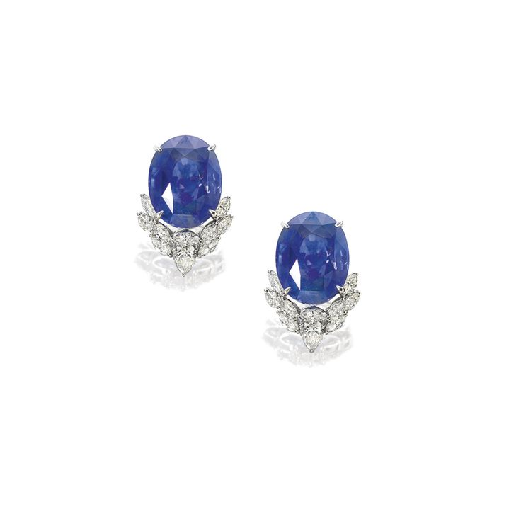 Pair of Sapphire and Diamond Earrings Each set with an oval sapphire weighing 21.35 and 21.29 carats respectively, embellished with variously-shaped diamonds weighing approximately 4.00 carats in total, mounted in 18 karat white gold, with clip and post fittings.