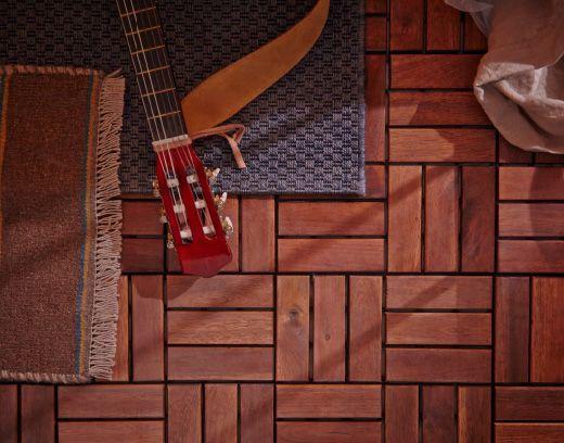 Blick aus der Vogelperspektive auf RUNNEN Bodenrost in Braun, bedeckt mit ein paar Teppichen. In der oberen linken Ecke ist eine Gitarre erkennbar.
