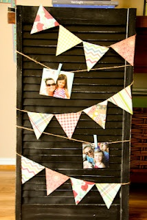 An old shutter, spray paint, scrapbook paper, photos, clothespins and twine....a photo display