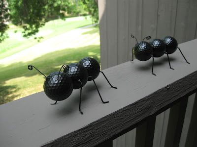 Wire coat hanger for legs, thinner wire for antennae (curl around a pencil), drill into place and hot glue them. Hot glue golf balls together, paint with house paint for extra durability.