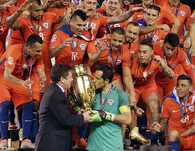 Chile goalkeeper Claudio Bravo kisses the Copa America trophy before lifting it…