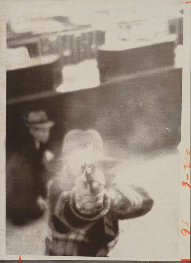 A photograph of a bank robber trying to shoot out security camera, 1975.