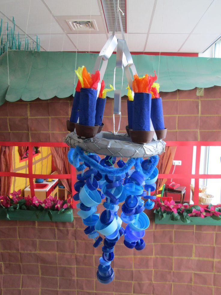 De kroonluchter boven de blauwe tafel gemaakt met doppen. Nutsschool Maastricht.